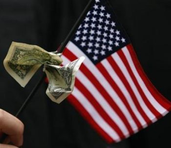 A student graduating from Harvard's Business School holds a U.S. flag with a dollar bill tied to it during the 357th Commencement Exercises at Harvard University in Cambridge, Massachusetts June 5, 2008.   REUTERS/Brian Snyder