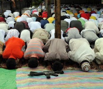 Members of the southern Philippine rebel group, the Moro Islamic Liberation Front (MILF), pray to celebrate the start of the three-day Eid al-Fitr feast, which marks the end of the holy Islamic month of Ramadan, at Camp Darapanan in Sultan Kudarat, in the Philippines' Maguindanao province, on Mindanao island on September 20, 2009. About five percent of Filipinos are Muslim, making them the largest minority in the mainly Roman Catholic nation. Muslims all over the world are set to begin the three-day holiday Eid marking the end of the fasting month of Ramadan. AFP PHOTO/TED ALJIBE (Photo credit should read TED ALJIBE/AFP/Getty Images)
